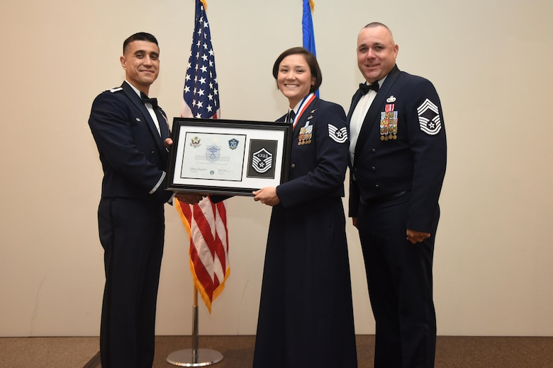 U.S. Air Force Tech. Sgt. Leanne Britt, 316th Training Squadron, receives their certificate of selection from Col. Ricky Mills, 17th Training Wing commander, and Chief Master Sgt. Daniel Stein, 17th Training Group superintendent, during the Senior NCO Induction Ceremony at the Event Center on Goodfellow Air Force Base, Texas, Aug. 18, 2017. (U.S. Air Force photo by Airman 1st Class Chase Sousa/Released)
