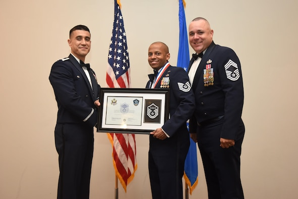 U.S. Air Force Tech. Sgt. Sheraz Cedeno, 17th Civil Engineer Squadron, receives their certificate of selection from Col. Ricky Mills, 17th Training Wing commander, and Chief Master Sgt. Daniel Stein, 17th Training Group superintendent, during the Senior NCO Induction Ceremony at the Event Center on Goodfellow Air Force Base, Texas, Aug. 18, 2017. (U.S. Air Force photo by Airman 1st Class Chase Sousa/Released)