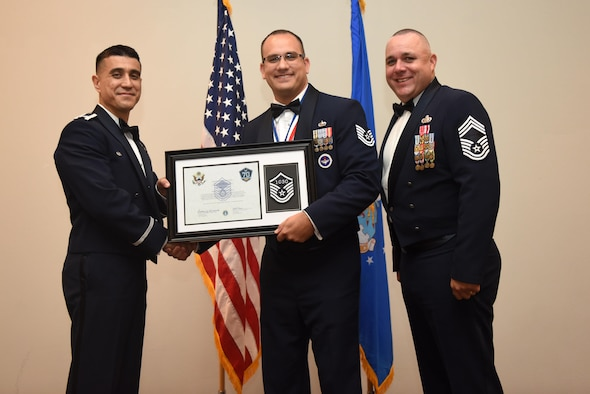 U.S. Air Force Tech. Sgt. Salvatore Corrao, 17th Training Support Squadron, receives their certificate of selection from Col. Ricky Mills, 17th Training Wing commander, and Chief Master Sgt. Daniel Stein, 17th Training Group superintendent, during the Senior NCO Induction Ceremony at the Event Center on Goodfellow Air Force Base, Texas, Aug. 18, 2017. (U.S. Air Force photo by Airman 1st Class Chase Sousa/Released)