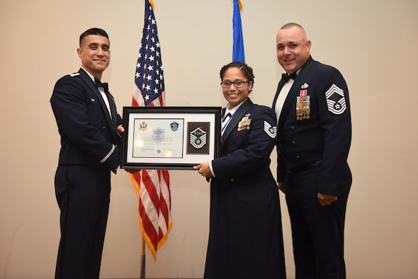U.S. Air Force Tech. Sgt. Stephanie Elliott, 17th Training Wing, receives their certificate of selection from Col. Ricky Mills, 17th Training Wing commander, and Chief Master Sgt. Daniel Stein, 17th Training Group superintendent, during the Senior NCO Induction Ceremony at the Event Center on Goodfellow Air Force Base, Texas, Aug. 18, 2017. (U.S. Air Force photo by Airman 1st Class Chase Sousa/Released)