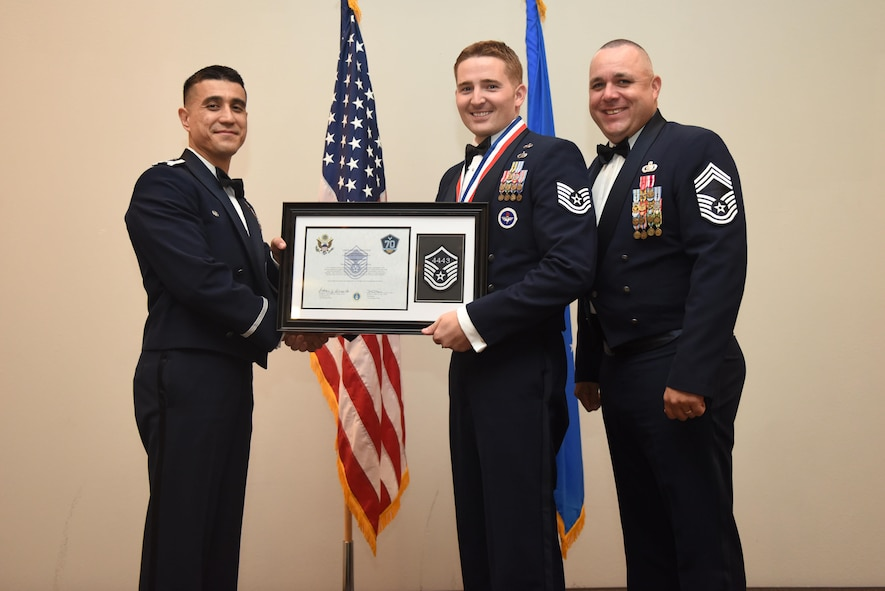 U.S. Air Force Tech. Sgt. Christopher Gibson, 315th Training Squadron, receives their certificate of selection from Col. Ricky Mills, 17th Training Wing commander, and Chief Master Sgt. Daniel Stein, 17th Training Group superintendent, during the Senior NCO Induction Ceremony at the Event Center on Goodfellow Air Force Base, Texas, Aug. 18, 2017. (U.S. Air Force photo by Airman 1st Class Chase Sousa/Released)