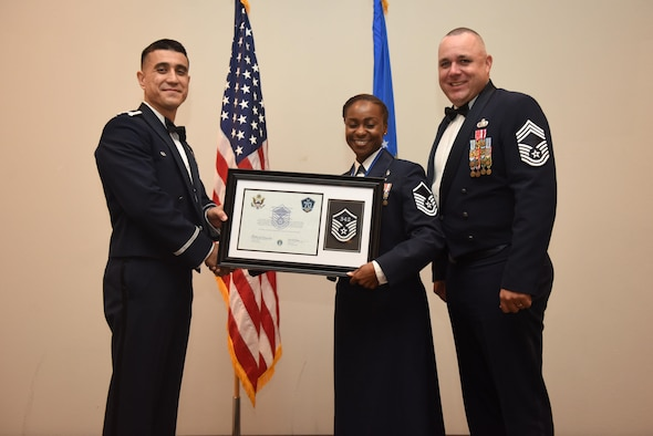 U.S. Air Force Master Sgt. Curtrell Gibson, 17th Force Support Squadron, receives their certificate of selection from Col. Ricky Mills, 17th Training Wing commander, and Chief Master Sgt. Daniel Stein, 17th Training Group superintendent, during the Senior NCO Induction Ceremony at the Event Center on Goodfellow Air Force Base, Texas, Aug. 18, 2017. (U.S. Air Force photo by Airman 1st Class Chase Sousa/Released)