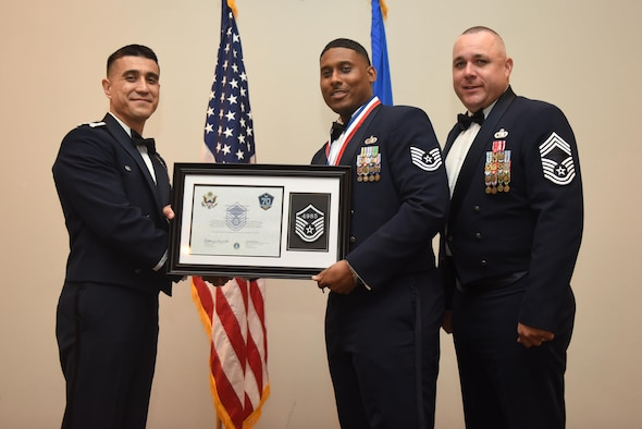 U.S. Air Force Tech. Sgt. James Gipson, 17th Force Support Squadron, receives their certificate of selection from Col. Ricky Mills, 17th Training Wing commander, and Chief Master Sgt. Daniel Stein, 17th Training Group superintendent, during the Senior NCO Induction Ceremony at the Event Center on Goodfellow Air Force Base, Texas, Aug. 18, 2017. (U.S. Air Force photo by Airman 1st Class Chase Sousa/Released)