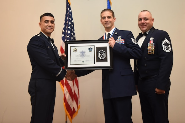 U.S. Air Force Tech. Sgt. Joseph King, 312th Training Squadron, receives their certificate of selection from Col. Ricky Mills, 17th Training Wing commander, and Chief Master Sgt. Daniel Stein, 17th Training Group superintendent, during the Senior NCO Induction Ceremony at the Event Center on Goodfellow Air Force Base, Texas, Aug. 18, 2017. (U.S. Air Force photo by Airman 1st Class Chase Sousa/Released)