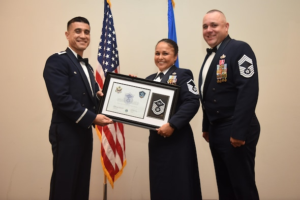 U.S. Air Force Master Sgt. Alexander Lewis, 315th Training Squadron, receives their certificate of selection from Col. Ricky Mills, 17th Training Wing commander, and Chief Master Sgt. Daniel Stein, 17th Training Group superintendent, during the Senior NCO Induction Ceremony at the Event Center on Goodfellow Air Force Base, Texas, Aug. 18, 2017. (U.S. Air Force photo by Airman 1st Class Chase Sousa/Released)