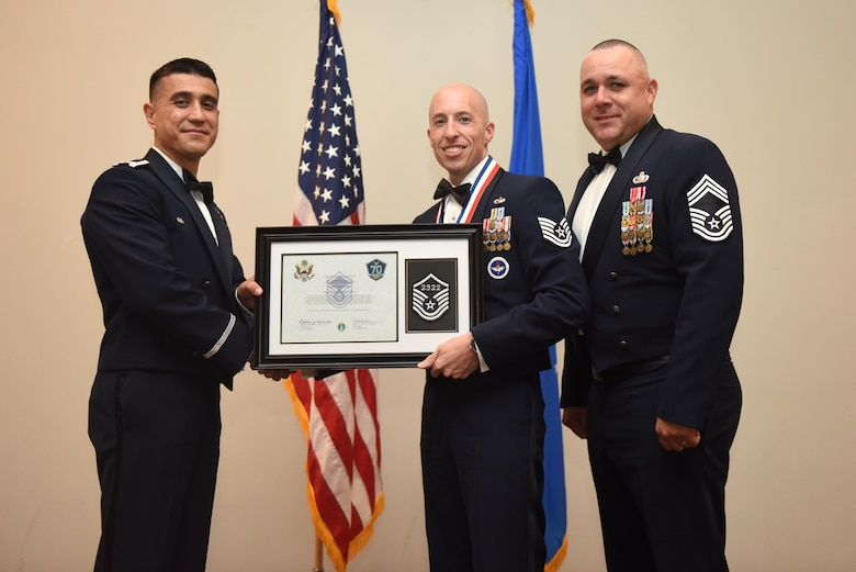 U.S. Air Force Tech. Sgt. Kirtis McCormick, 315th Training Squadron, receives their certificate of selection from Col. Ricky Mills, 17th Training Wing commander, and Chief Master Sgt. Daniel Stein, 17th Training Group superintendent, during the Senior NCO Induction Ceremony at the Event Center on Goodfellow Air Force Base, Texas, Aug. 18, 2017. (U.S. Air Force photo by Airman 1st Class Chase Sousa/Released)