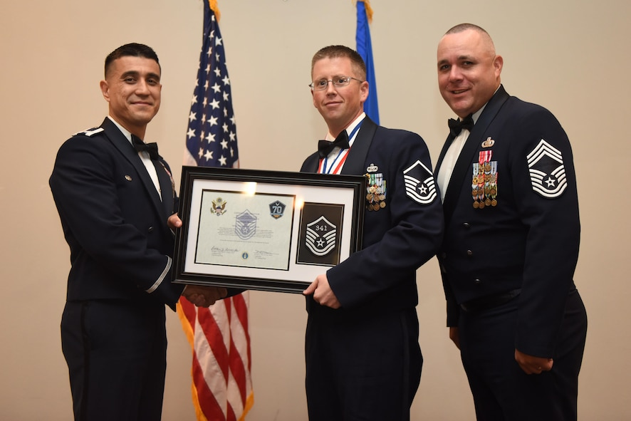 U.S. Air Force Master Sgt. Nathanael Meagher, 17th Force Support Squadron, receives their certificate of selection from Col. Ricky Mills, 17th Training Wing commander, and Chief Master Sgt. Daniel Stein, 17th Training Group superintendent, during the Senior NCO Induction Ceremony at the Event Center on Goodfellow Air Force Base, Texas, Aug. 18, 2017. (U.S. Air Force photo by Airman 1st Class Chase Sousa/Released)