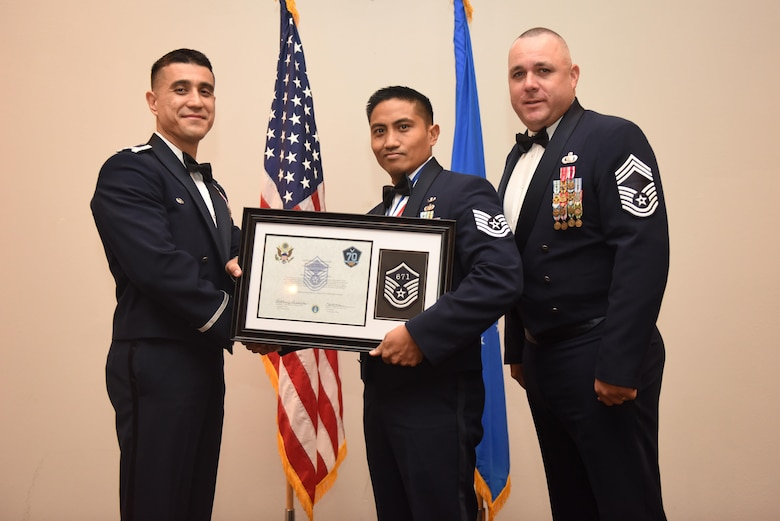 U.S. Air Force Tech. Sgt. Johnny Patubo, 17th Communications Squadron, receives their certificate of selection from Col. Ricky Mills, 17th Training Wing commander, and Chief Master Sgt. Daniel Stein, 17th Training Group superintendent, during the Senior NCO Induction Ceremony at the Event Center on Goodfellow Air Force Base, Texas, Aug. 18, 2017. (U.S. Air Force photo by Airman 1st Class Chase Sousa/Released)