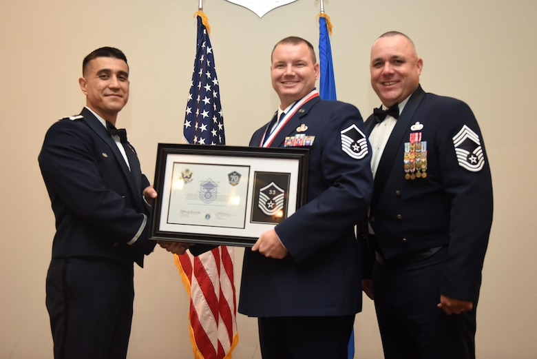 U.S. Air Force Master Sgt. Bruce Perkins, 17th Training Support Squadron, receives their certificate of selection from Col. Ricky Mills, 17th Training Wing commander, and Chief Master Sgt. Daniel Stein, 17th Training Group superintendent, during the Senior NCO Induction Ceremony at the Event Center on Goodfellow Air Force Base, Texas, Aug. 18, 2017. (U.S. Air Force photo by Airman 1st Class Chase Sousa/Released)