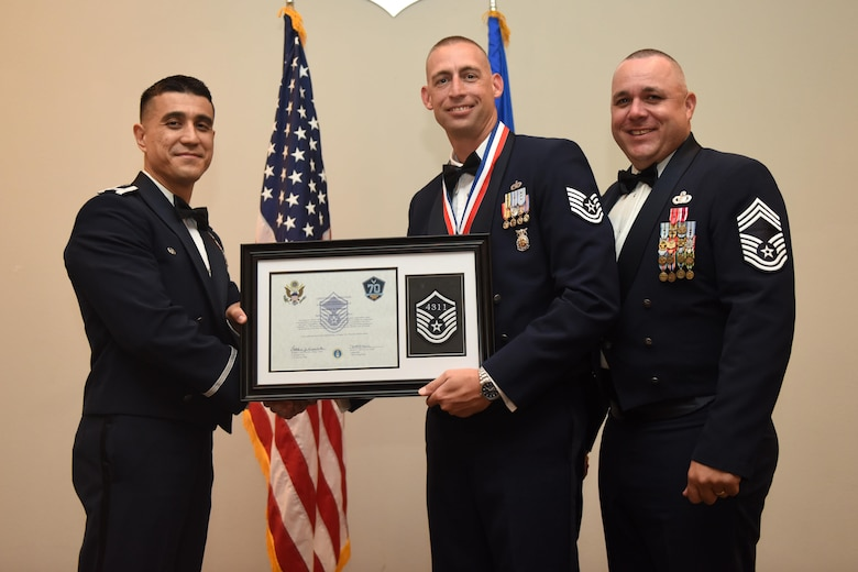 U.S. Air Force Tech. Sgt. Nicholas Schnoes, 312th Training Squadron, receives their certificate of selection from Col. Ricky Mills, 17th Training Wing commander, and Chief Master Sgt. Daniel Stein, 17th Training Group superintendent, during the Senior NCO Induction Ceremony at the Event Center on Goodfellow Air Force Base, Texas, Aug. 18, 2017. (U.S. Air Force photo by Airman 1st Class Chase Sousa/Released)