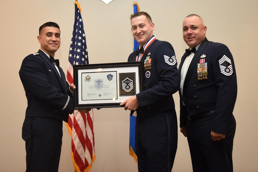 U.S. Air Force Tech. Sgt. Martin Smith, 315th Training Squadron, receives their certificate of selection from Col. Ricky Mills, 17th Training Wing commander, and Chief Master Sgt. Daniel Stein, 17th Training Group superintendent, during the Senior NCO Induction Ceremony at the Event Center on Goodfellow Air Force Base, Texas, Aug. 18, 2017. (U.S. Air Force photo by Airman 1st Class Chase Sousa/Released)