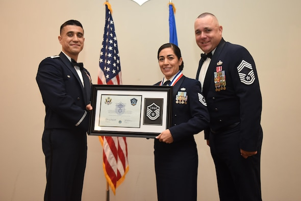 U.S. Air Force Tech. Sgt. Rosanna Surber, 17th Comptroller Squadron, receives their certificate of selection from Col. Ricky Mills, 17th Training Wing commander, and Chief Master Sgt. Daniel Stein, 17th Training Group superintendent, during the Senior NCO Induction Ceremony at the Event Center on Goodfellow Air Force Base, Texas, Aug. 18, 2017. (U.S. Air Force photo by Airman 1st Class Chase Sousa/Released)