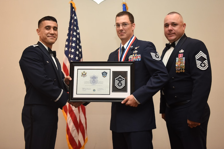 U.S. Air Force Tech. Sgt. David Syring, 316th Training Squadron, receives their certificate of selection from Col. Ricky Mills, 17th Training Wing commander, and Chief Master Sgt. Daniel Stein, 17th Training Group superintendent, during the Senior NCO Induction Ceremony at the Event Center on Goodfellow Air Force Base, Texas, Aug. 18, 2017. (U.S. Air Force photo by Airman 1st Class Chase Sousa/Released)