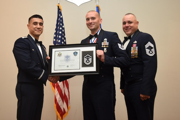 U.S. Air Force Tech. Sgt. Jeffrey Trueman, 312th Training Squadron, receives their certificate of selection from Col. Ricky Mills, 17th Training Wing commander, and Chief Master Sgt. Daniel Stein, 17th Training Group superintendent, during the Senior NCO Induction Ceremony at the Event Center on Goodfellow Air Force Base, Texas, Aug. 18, 2017. (U.S. Air Force photo by Airman 1st Class Chase Sousa/Released)