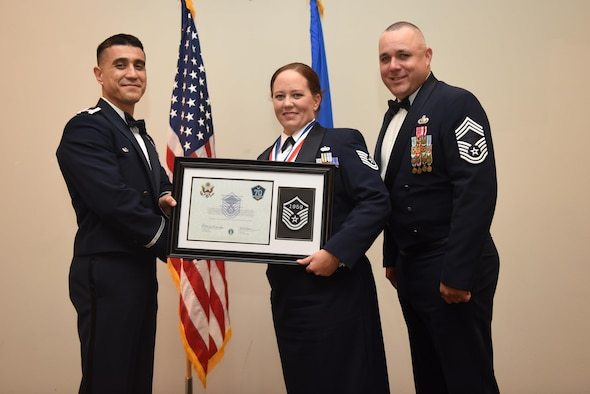 U.S. Air Force Tech. Sgt. Jessica Turner, 17th Force Support Squadron, receives their certificate of selection from Col. Ricky Mills, 17th Training Wing commander, and Chief Master Sgt. Daniel Stein, 17th Training Group superintendent, during the Senior NCO Induction Ceremony at the Event Center on Goodfellow Air Force Base, Texas, Aug. 18, 2017. (U.S. Air Force photo by Airman 1st Class Chase Sousa/Released)
