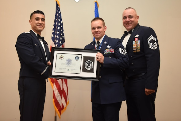U.S. Air Force Tech. Sgt. Jeremy Vonada, 316th Training Squadron, receives their certificate of selection from Col. Ricky Mills, 17th Training Wing commander, and Chief Master Sgt. Daniel Stein, 17th Training Group superintendent, during the Senior NCO Induction Ceremony at the Event Center on Goodfellow Air Force Base, Texas, Aug. 18, 2017. (U.S. Air Force photo by Airman 1st Class Chase Sousa/Released)