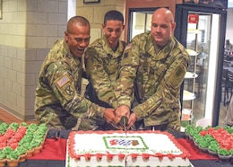 Pvt. Julio Angel Diaz Rivera, center, a tank driver with 3rd Battalion, 66th Armored Regiment, 1st Armored Brigade Combat Team, 1st Infantry Division; Command Sgt. Maj. Mulivai Matau, 1st Bn., 16th Inf. Regt., 1st ABCT, senior noncommissioned officer; and Col. Charles Armstrong, 1st ABCT commander; cut a celebratory cake during the grand reopening of the 1st ABCT dining facility, the Devil's Den, Aug. 7. The grand reopening followed a remodeling of the facility and updating of the menu.