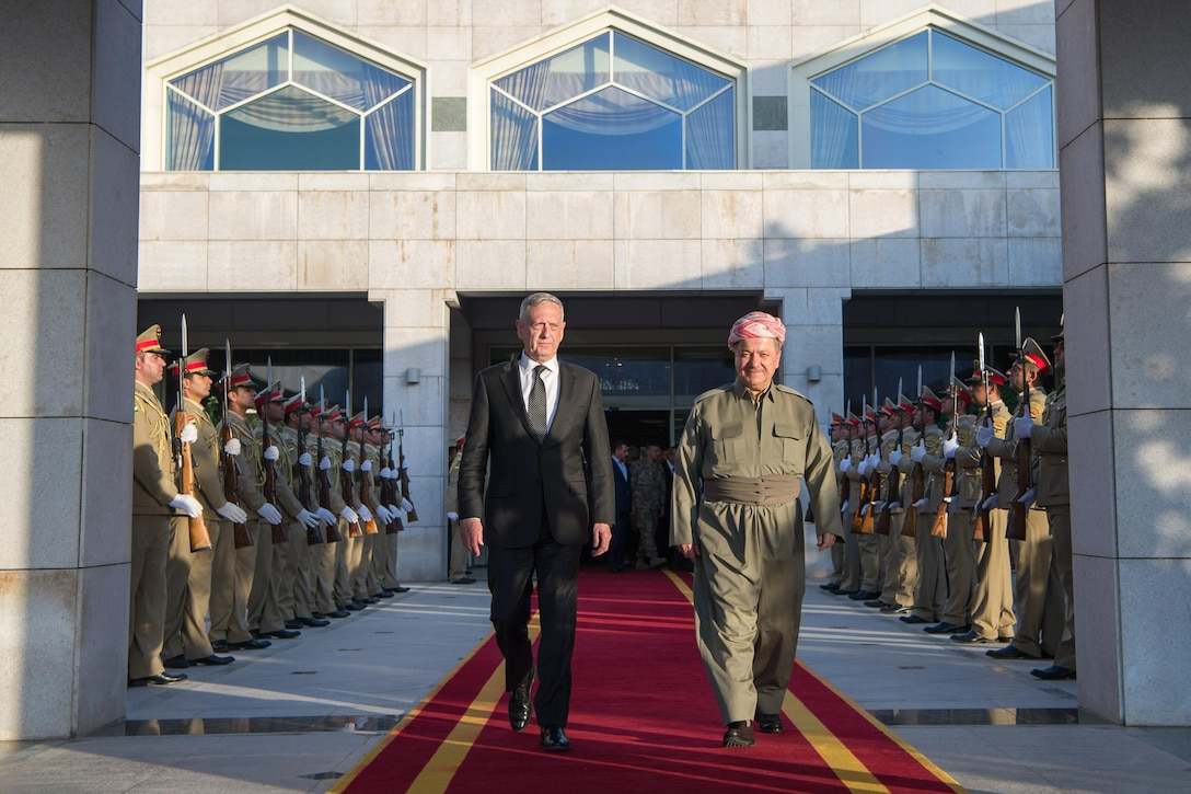 Two leaders walk along a red carpet in Iraq.