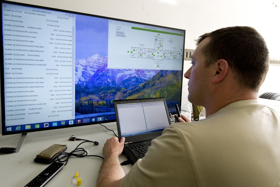 Former U.S. Air Force Capt. Chris Perrine, Air Force Life Cycle Management Center, chief of acquisitions for net centric services-2, from Robbins Air Force Base, Ga., monitors his team's active shooter detection system during the 2015 Air Force Research Laboratory Commander's Challenge.