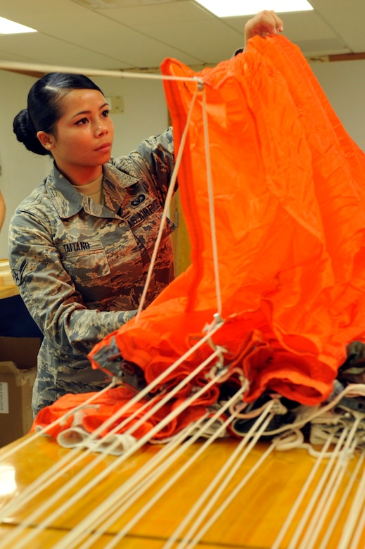 Airman Laura Taitano, 56th Operation Support Squadron aircrew flight equipment apprentice, inspects a parachute August 18,2017, at Luke Air Force Base, Ariz. These types of parachutes are maintained and packed for Taiwan fighter pilots. (U.S. Air Force photo/Airman 1st Class Pedro Mota)