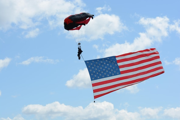 A member of the Black Daggers U.S. Army Special Operations Command parachute demo team displays the American flag on his descent August 13, 2017, at the 2017 Westfield International Air Show at Barnes Air National Guard  Base in Westfield, Mass.