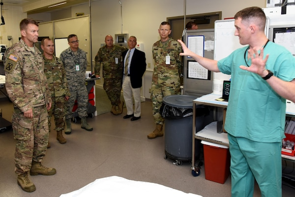 Lt. Gen. Jeffrey Buchanan, U.S. Army North Commanding General, left, gets a brief of the research operating room by Spc. Alexander Dixon during a tour of the U.S. Army Institute of Surgical Research at Fort Sam Houston, Texas as U.S. Army North Command Sgt. Maj. Ronald Orosz, USAISR Deputy Commander, Col. (Dr.) Erik Weitzel, Sgt. Maj. William Poist, Anthony Pusateri, Ph.D., and Lt. Col. (Dr.) Ammon Brown look on.