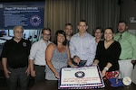 Group of civilians facing viewer, holding sheet cake