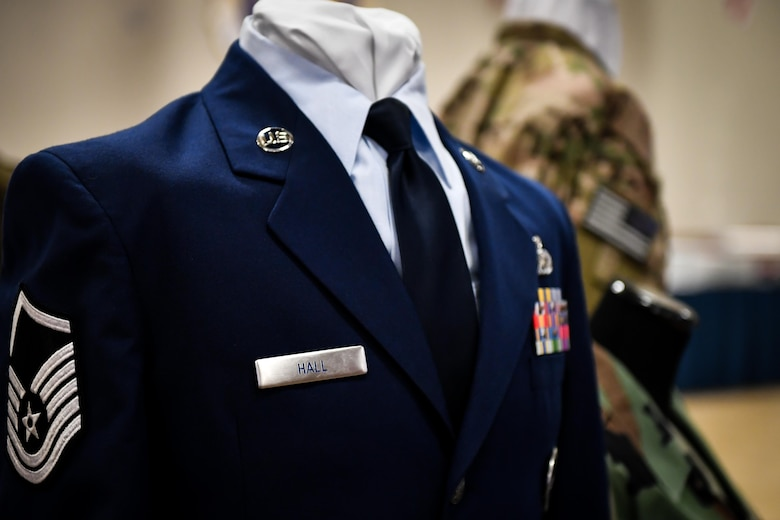 Uniforms from different eras are displayed with master sergeant Stripes during the 2017 Senior NCO induction ceremony at Barksdale Air Force Base, La., Aug. 18. The uniform display included a current service dress uniform, an out of service Battle Dress Uniform and a flight suit.