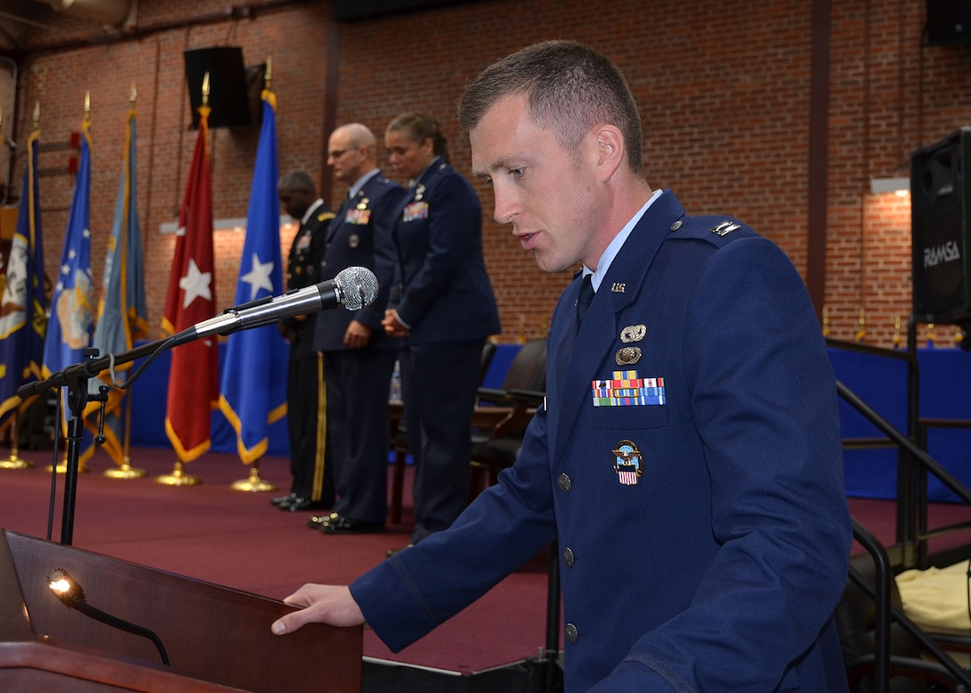 Capt. Musleve stands at a podium and narrates the 2017 DLA Aviation Change of Command Ceremony.