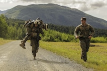 U.S. Marines with 1st Battalion, 25th Marine Regiment, 4th Marine Division, Marine Forces Reserve and members of 1st Squad fireman carry one another while completing a timed grenade assault range during the Combat Marksmanship Endurance Test in the Small Arms Complex on Joint Base Elmendorf-Richardson, Alaska, Aug. 8, 2017.