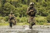U.S. Marines with Super Squad Competition 1st Squad, out of 1st Battalion, 25th Marine Regiment, 4th Marine Division, Marine Forces Reserve, conduct a river crossing during the Combat Marksmanship Endurance Test Phase II on Joint Base Elmendorf-Richardson, Alaska, Aug. 8, 2017.