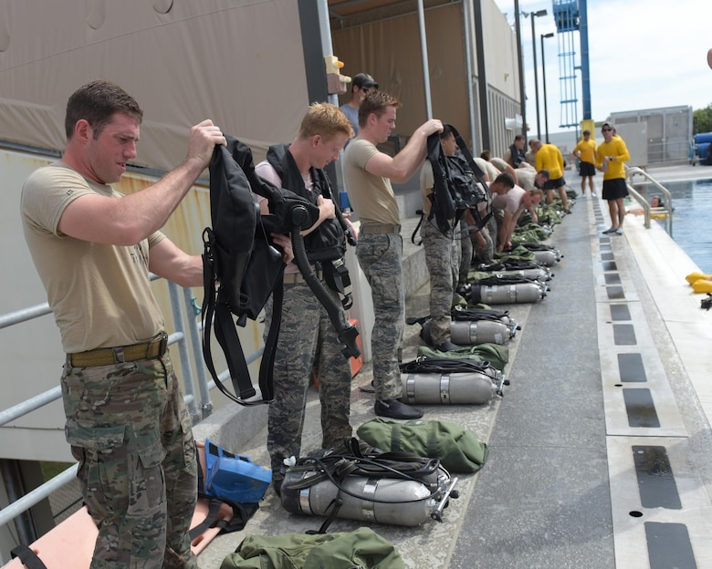 U.S. Air Force dive school students get their equipment ready for a training session at Naval Support Activity Panama City, Fla., Aug. 2, 2017. Both pararescue and combat controller Airmen get their dive training at the Naval Diving and Salvage Training Center.