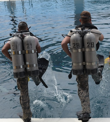U.S. Air Force diving students step into a pool for a training exercise at Naval Support Activity Panama City, Fla., Aug. 2. 2017. The Naval Diving and Salvage Training Center is the Department of Defense's largest dive school and trains members of all five military branches.