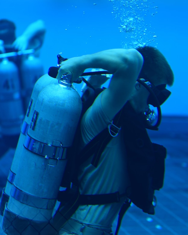 A U.S. Air Force diving student adjusts his air tank during an underwater exercise at Naval Support Activity Panama City, Fla., Aug. 3, 2017. The training involved testing the students on whether they were able to put their diving gear on while already underwater. This would test their ability to operate under emergency situations.