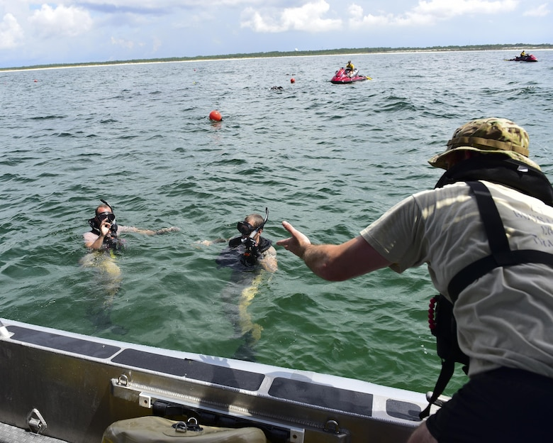 Naval Diving and Salvage Training Center students consult with one another during a training exercise in the Gulf of Mexico, Aug. 15, 2017. Air Force combat rescue officers also go through the same training alongside their enlisted counterparts during this course.