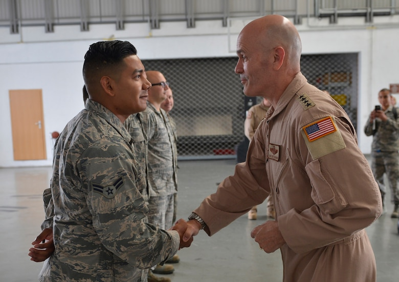 General shakes Airman's hand