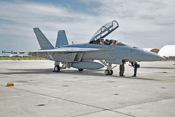 """Lt. Drew Kocher and Lt. Cmdr. Brad Williams, both assigned to the """"Fighting Swordsman"""" of Strike Fighter Squadron (VFA) 32, landed on Naval Air Station Key West's Boca Chica Field after completing Tactical Combat Training System's 100,000th pod-tracked sortie since the system began tracking using GPS technology in 2006."""