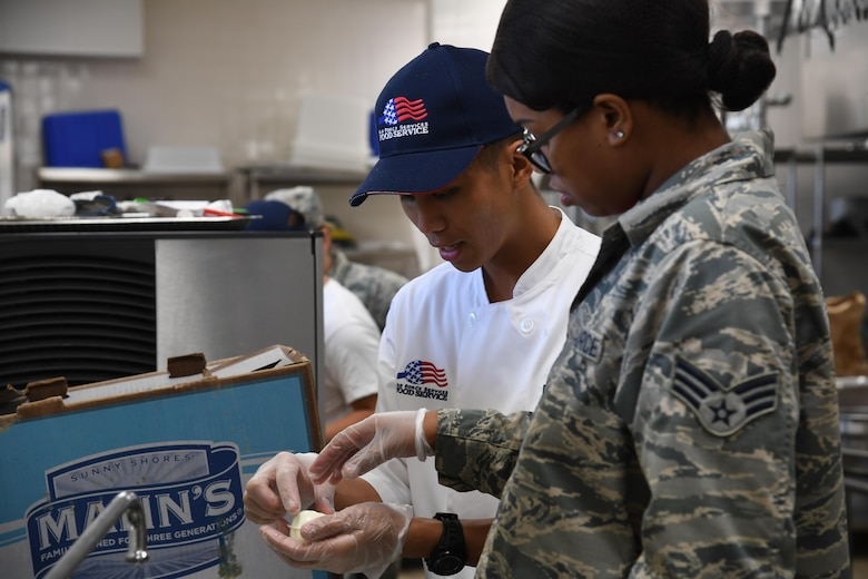 Airman 1st Class Lester Torres, 2nd Force Support Squadron food services apprentice prepares a garnish during an advanced culinary skills course graduation at the Red River Dining Facility at Barksdale Air Force Base, La., Aug. 18, 2017.Torres, demonstrated to other Airmen how to create a garnish using a hardboiled egg.