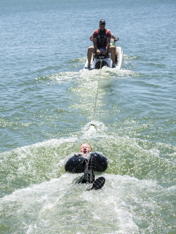 A pilot is dragged behind a jet ski during water survival training July 11, 2017, at CJ Strike Reservoir, Idaho. This portion of training teaches proper technique when hitting the water and being dragged by an open parachute. (U.S. Air Force photo by Airman 1st Class Jeremy D. Wolff/Released)