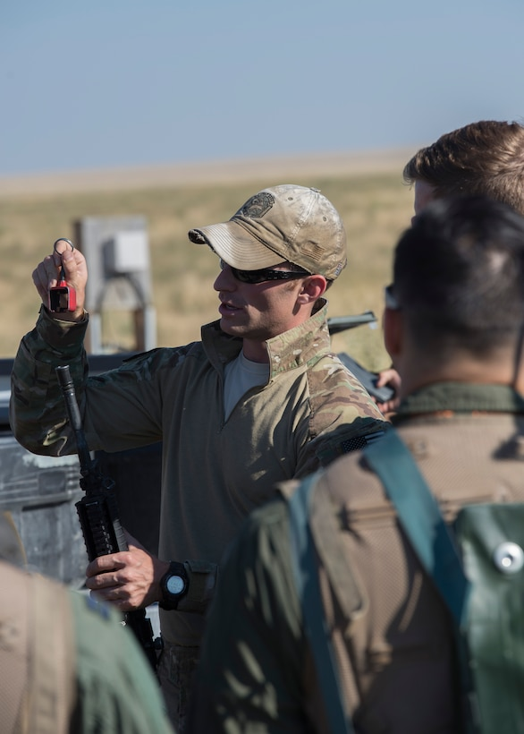 Staff Sgt. Cassidy Steffen, 366th Operations Support Squadron survival, evasion, resistance and escape specialist demonstrates how to secure a blank firing adapter during Combat Survival Training August 17, 2017, at Mountain Home Air Force Base, Idaho. CST is an in depth exercise that tests pilot's abilities to evade enemy forces and put themselves in the best position to be rescued. (U.S. Air Force photo by Airman 1st Class Jeremy D. Wolff/Released)