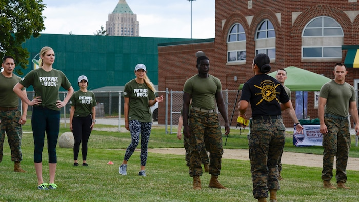 Kate Upton and others listen to instructions from GySgt. Sara Pacheco before they executed a workout at Wayne State University's athletic complex in Detroit on Aug. 22, 2017. Upton and others completed a circuit course consisting of several rounds of burpees, sprints, jumping jacks and more in an effort to promote Marine Week Detroit that takes place Sept. 6-10. Marine Week Detroit is a four-day event that will showcase hands-on static displays, live demonstrations, time-honored Marine Corps traditions, musical performances and other events highlighting the history, military capabilities and community involvement of the Corps.