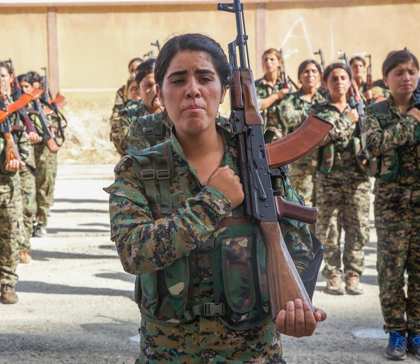 Syrian Democratic Forces trainees, representing an equal amount of Arab and Kurdish volunteers, stand in formation.
