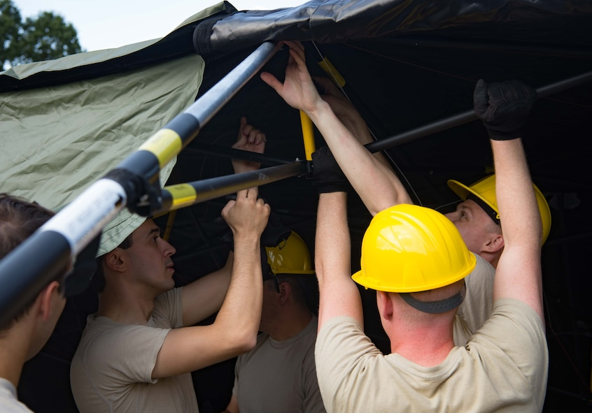 U.S. Airmen assigned to the 1st Combat Communications Squadron repair and assemble a communications tent during Exercise Lending Hand on Ramstein Air Base, Germany, Aug. 21, 2017.