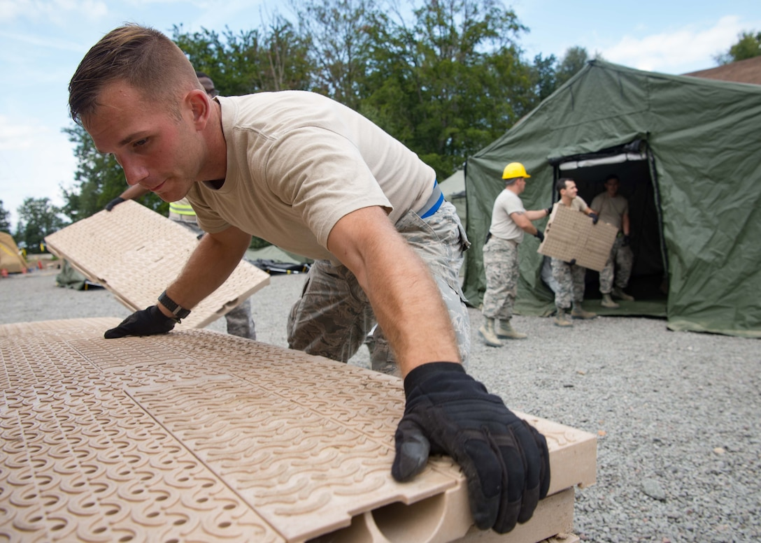 U.S. Air Force Senior Airman Zackery Powers, 1st Combat Communications Squadron radio frequency technician, hands flooring tiles to an assembly line to construct a communications tent during Exercise Lending Hand on Ramstein Air Base, Germany, Aug. 21, 2017.