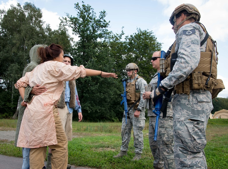 Exercise Lending Hand participants roleplaying as refugees, left, ask U.S. Airmen for water and medical attention during Exercise Lending Hand on Ramstein Air Base, Germany, Aug. 21, 2017.