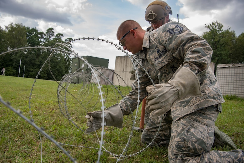 U.S. Air Force Tech. Sgt. Mark Kegel, 435th Security Forces Squadron Phoenix Fist team leader, lays barbed wire around the perimeter of a simulated base during Exercise Lending Hand on Ramstein Air Base, Germany, Aug. 21, 2017.