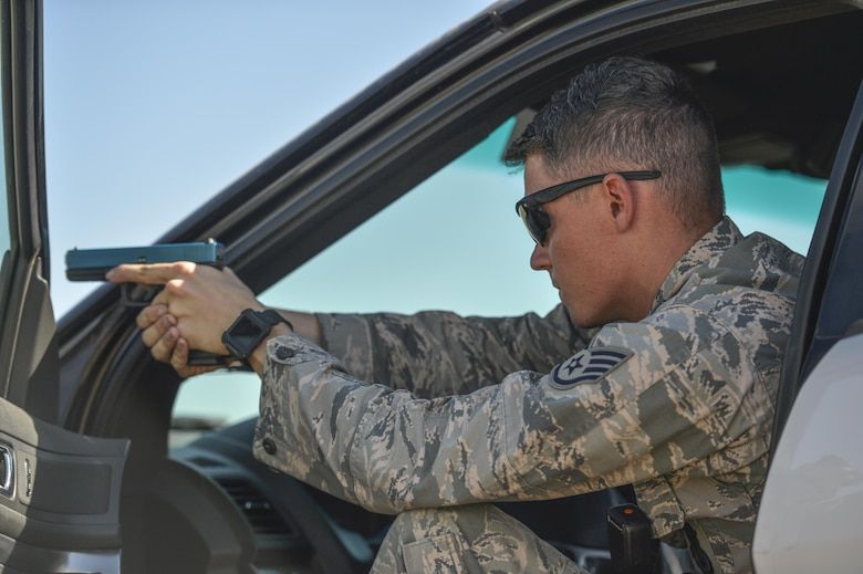 Staff Sgt. Ryan Kneafsey, 56th Security Forces Squadron unit trainer, assists with the apprehension of a suspect arrest during an exercise as part of an Emergency Vehicle Operations Course held at Luke Air Force Base, Ariz., Aug. 21, 2017. Kneafsey and several other 56 SFS members participated in different segments of vehicle backing, braking, pursuit driving and high-risk stops. (U.S. Air Force photo/Airman 1st Class Caleb Worpel)