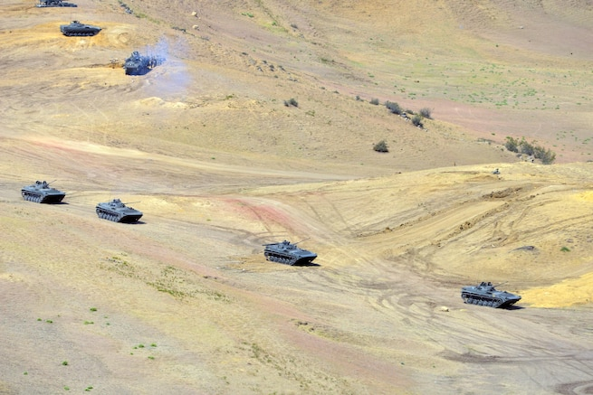 Military vehicles drive though hilly terrain.