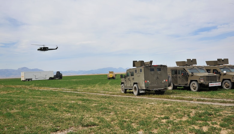 A UH-1N Iroquois helicopter from the 40th Helicopter Squadron circles over a payload transporter and security forces vehicles assigned to the 341st Missile Wing prior to the start of the Local Integrated Response Plan exercise Aug. 16, 2017, near Choteau, Mont.