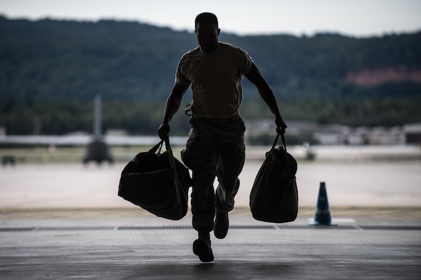 U.S. Air Force Staff Sgt. Kenneth Welch, 86th Aircraft Maintenance Squadron communications countermeasures navigation systems craftsman, runs with equipment bags during a relay race at the Maintainer Olympics in the dual hangar bay on Ramstein Air Base, Germany, Aug. 24, 2017.